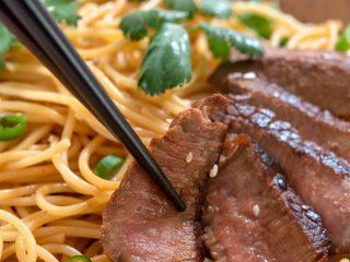 Chopsticks picking up slice of beef steak with sesame noodles