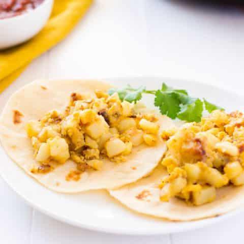 A plate with two papas con huevos (potato and egg tacos)