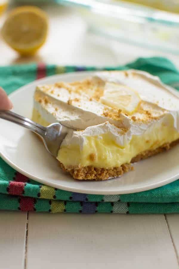 This luscious lemon cheesecake pudding dessert is a no-bake dream! Made with a graham cracker crust, lemon pudding, cream cheese and cool whip!