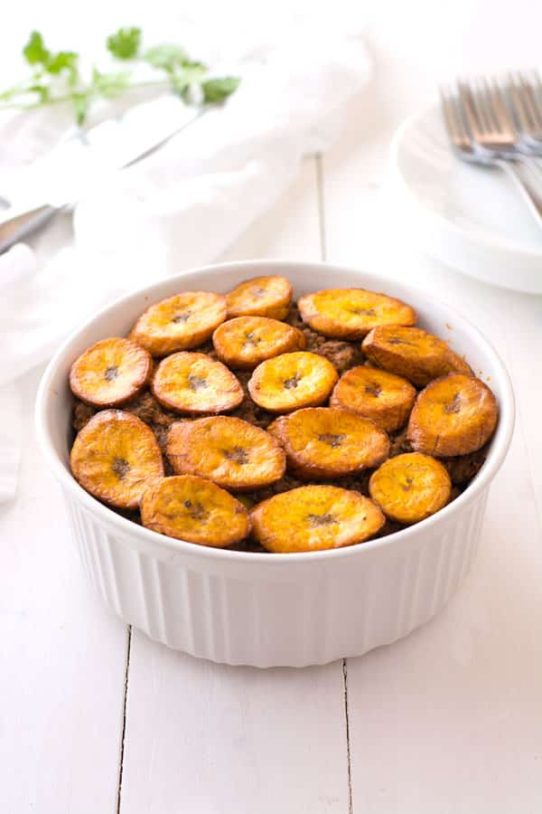 Piñon is a hearty plantain casserole made with layers of picadillo, fried ripe plantains, kidney beans and green beans. Try this Puerto Rican beef and plantain piñon recipe today!