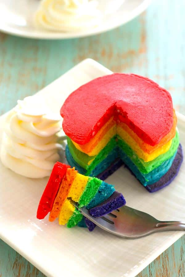 "Serve these rainbow pancakes for St. Patrick's Day breakfast! Colored pancakes with fluffy ""clouds"" of whipped cream are lucky indeed!"