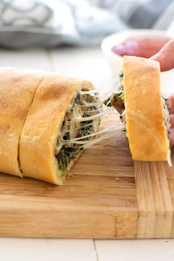 Stuffed Spinach Bread loaf rolled up with cheese and sausage. This cheesy spinach appetizer is amazing!