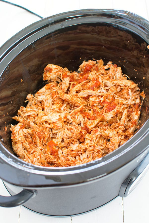 Black crockpot with cooked chicken for slow cooker chicken parmesan sliders
