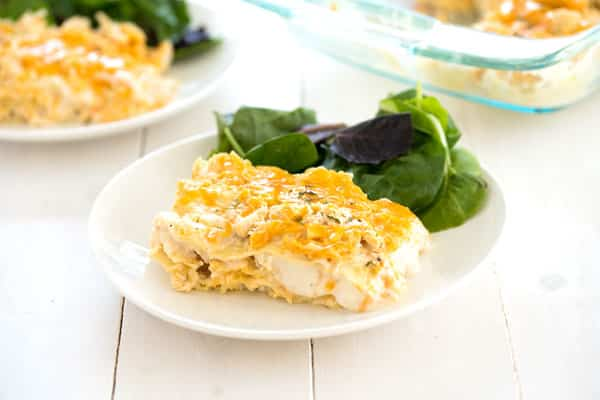 Slice of white chicken lasagna with a salad for an easy dinner recipe!