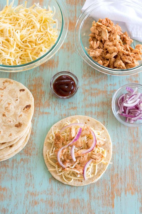 BBQ Chicken Quesadilla ingredients - cheese, chicken, sauce, onion, tortillas