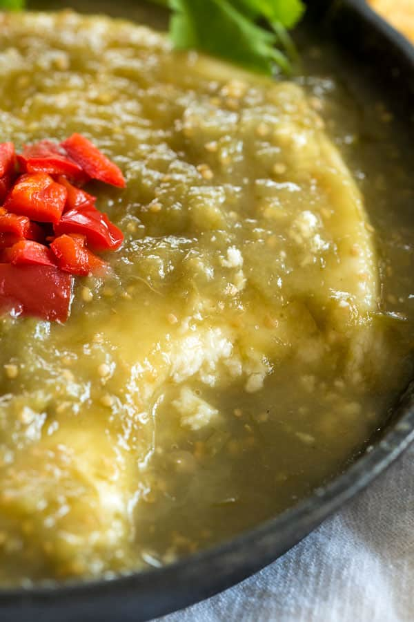 Baked Queso Fresco Dip in green salsa verde. Serve this appetizer in a cast iron skillet with chips!