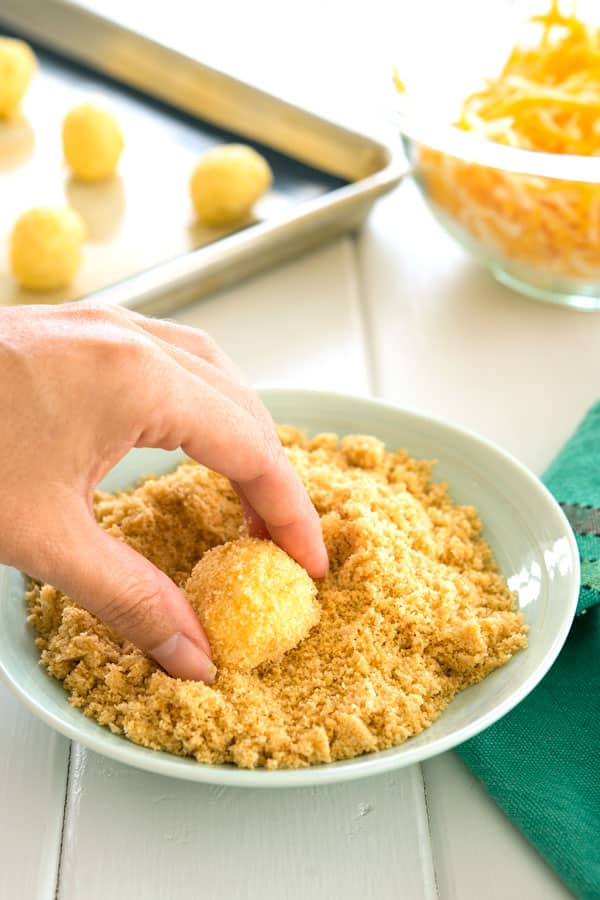 Rolling bolitas de queso (fried cheese balls) in cracker crumbs before frying