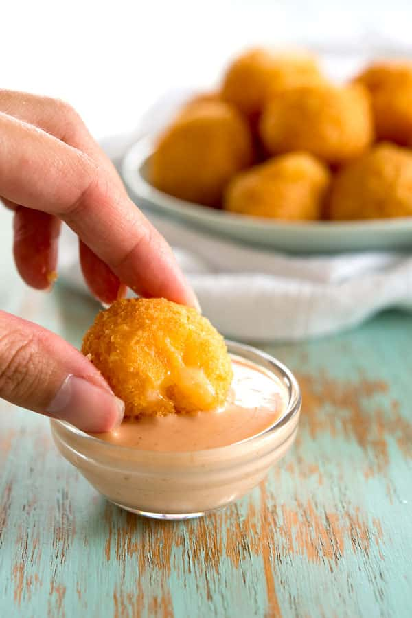 Dipping bolitas de queso (fried cheese balls) in mayoketchup
