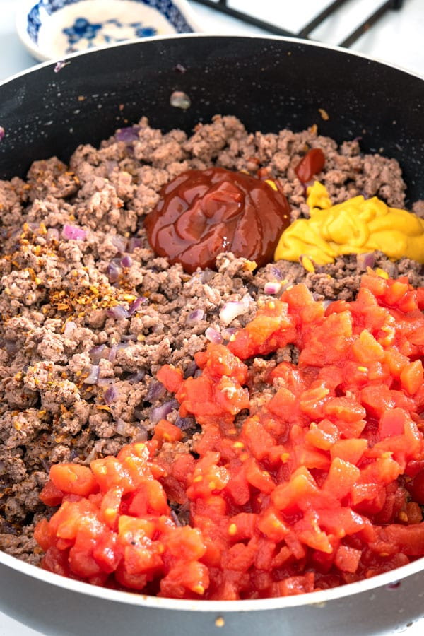 Skillet with ingredients for cheeseburger tater tot casserole - ground beef, tomatoes, ketchup, mustard