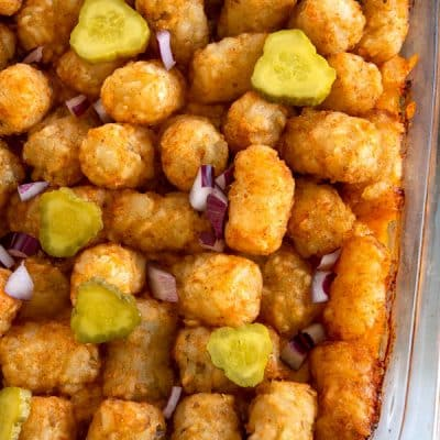 Overhead shot of cheeseburger tater tot casserole topped with pickles and onions