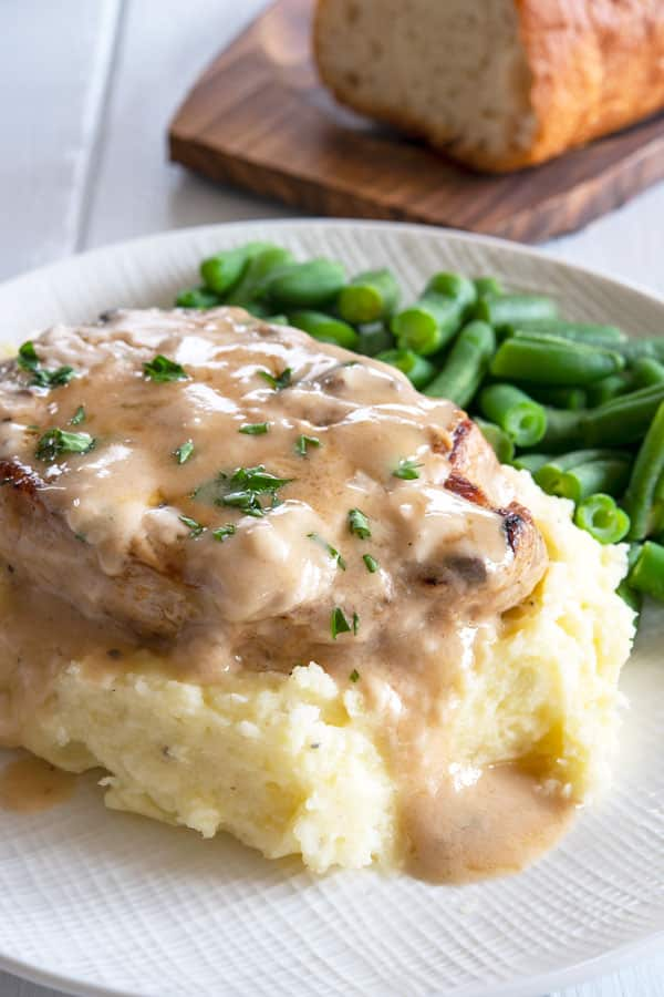 Baked pork chop on mashed potatoes with a side of green beans