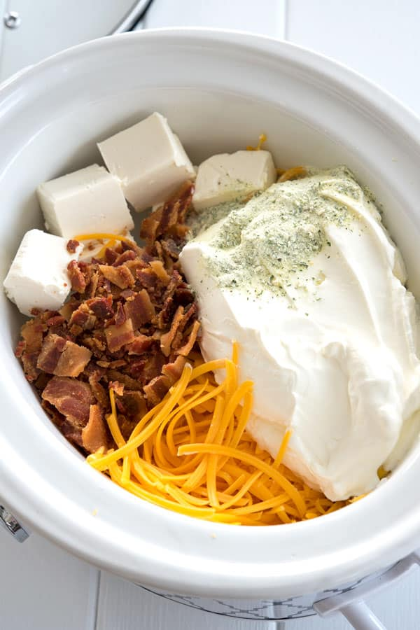 Ingredients for crock pot crack dip in crock: cream cheese, sour cream, bacon, cheddar and ranch mix