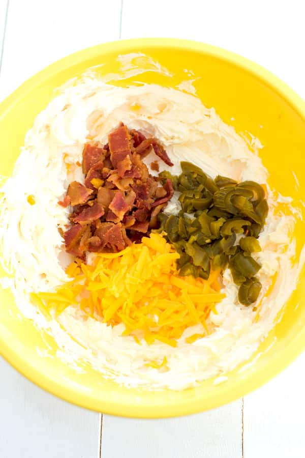 Yellow mixing bowl with cream cheese, bacon, cheddar cheese and jalapenos