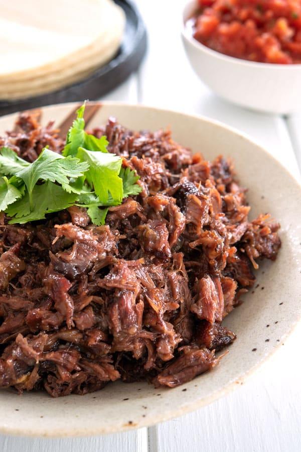 Platter of shredded beef cheek barbacoa with cilantro garnish
