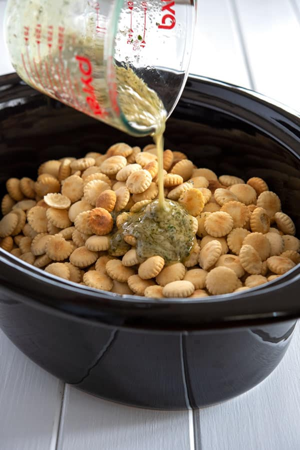 Melted butter with seasonings being poured over oyster crackers in a crock pot