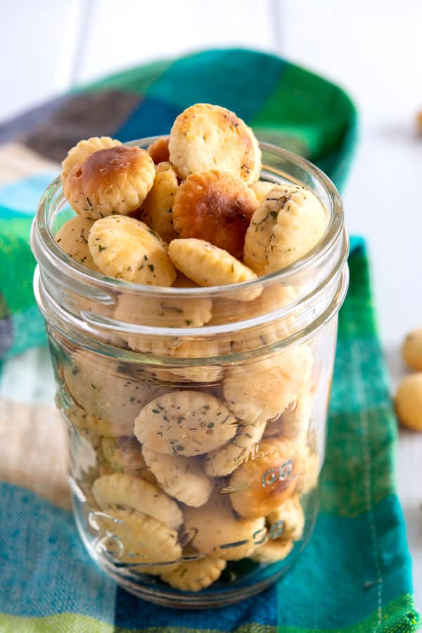 Small mason jar full of ranch oyster crackers with a teal blue green checkered cloth background