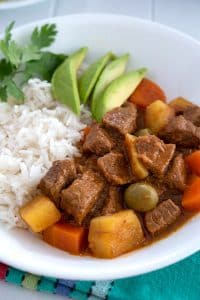 Puerto Rican Carne Guisada served with rice and sliced avocado