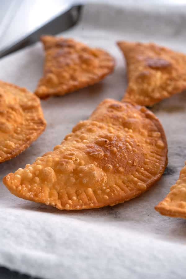 Fried buffalo chicken empanadas draining on paper towels