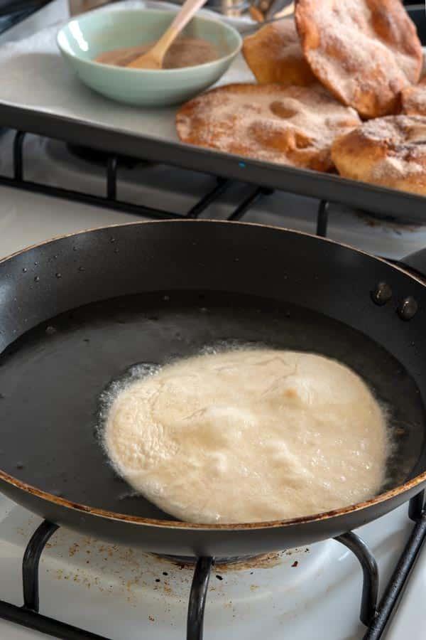 Flour tortilla frying in oil for Easy Buñuelos Recipe