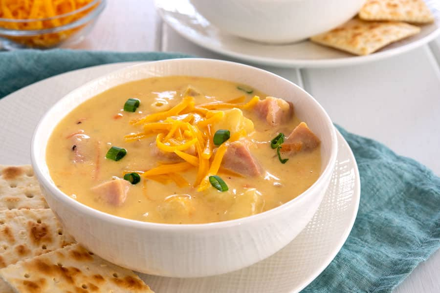 Bowl of cheesy ham and potato soup with cheddar, potatoes and green onions