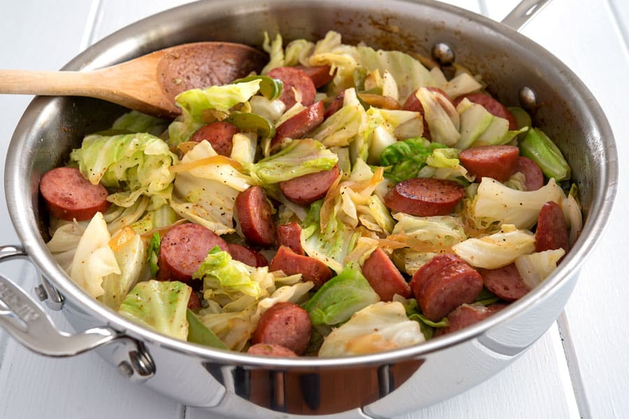 Kielbasa and cabbage in large, silver all-clad skillet