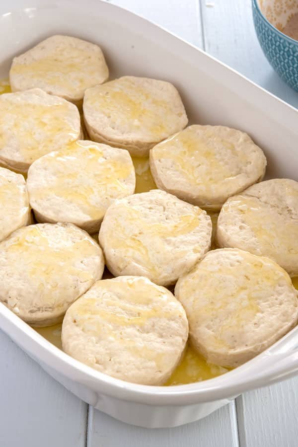 Raw biscuits in baking dish drizzled with butter before baking