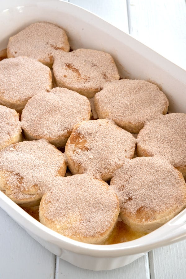 Raw biscuits in baking dish sprinkled with cinnamon sugar before baking