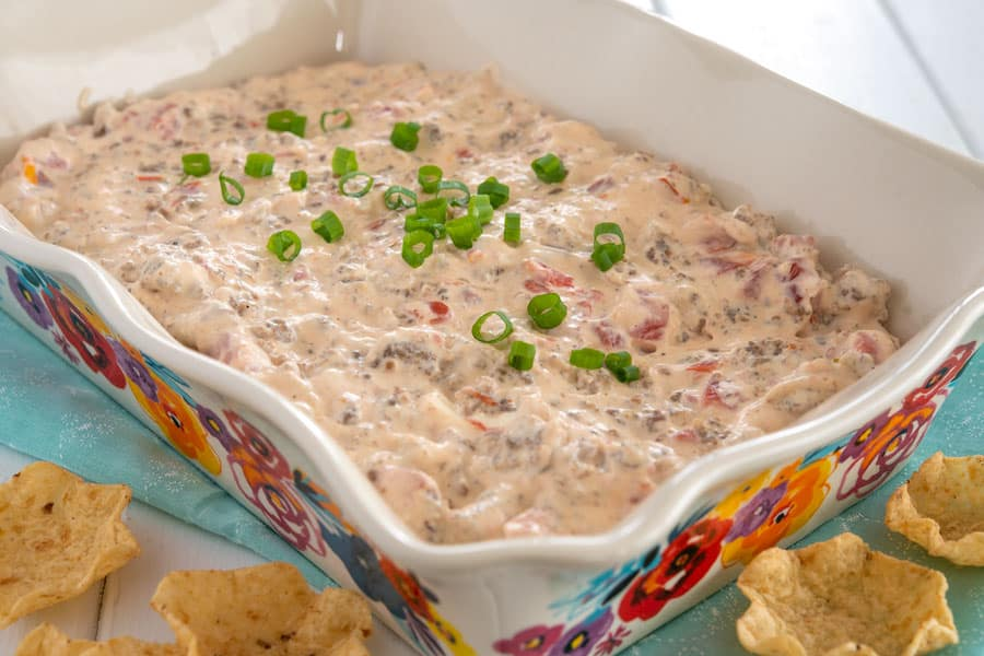 Sausage cream cheese dip in serving dish garnished with green onions