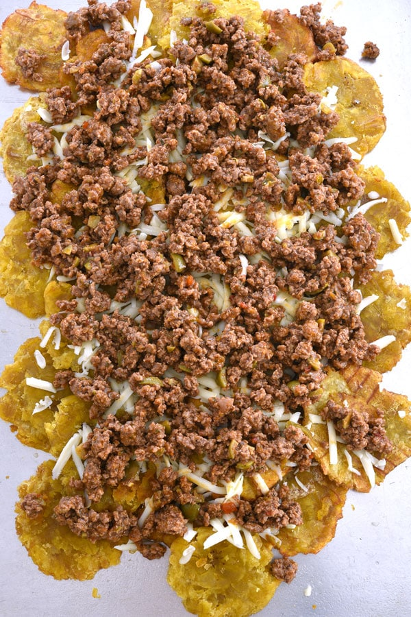 Layers of tostones, cheese and picadillo on cookie sheet for tostone nachos