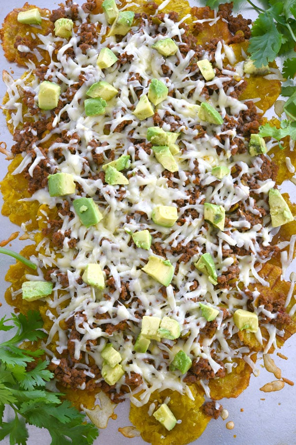 Overhead shot of tostone nachos layered with cheese, picadillo and avocado