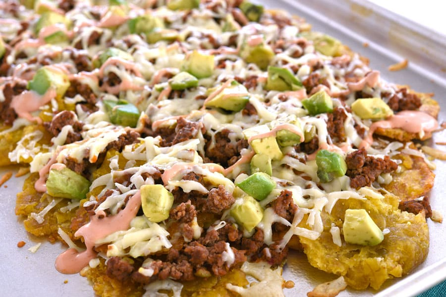 Pan of tostone nachos layered with ground beef, cheese, avocado and mayoketchup