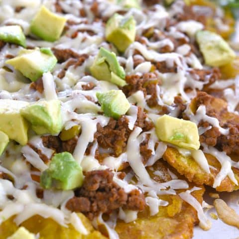 Sheet pan of tostone nachos layered with cheese, picadillo and avocado
