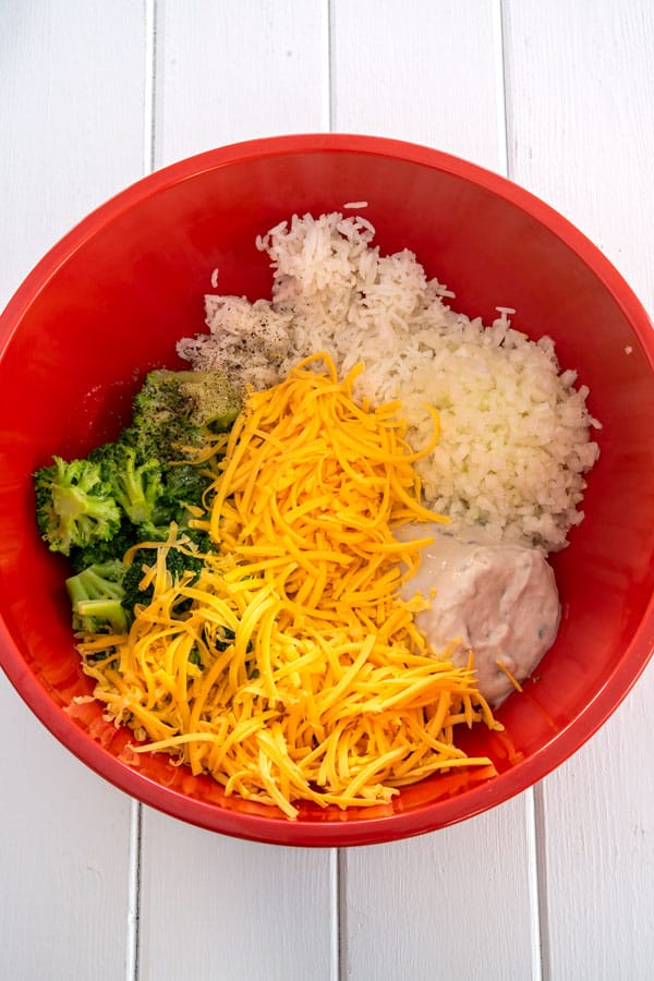 Red bowl with broccoli cheese rice casserole ingredients ready to mix