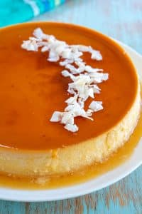 Flan de Coco on a white plate garnished with shredded coconut