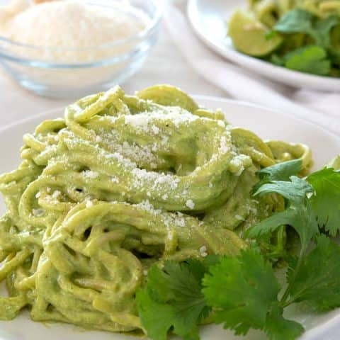 White plate with espagueti verde garnished with grated cheese and cilantro