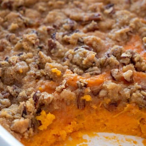 White casserole dish of sweet potato casserole with pecans and brown sugar topping