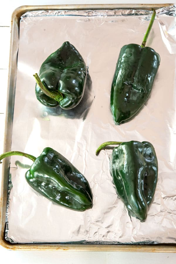 Four poblano peppers on a baking tray for roasting