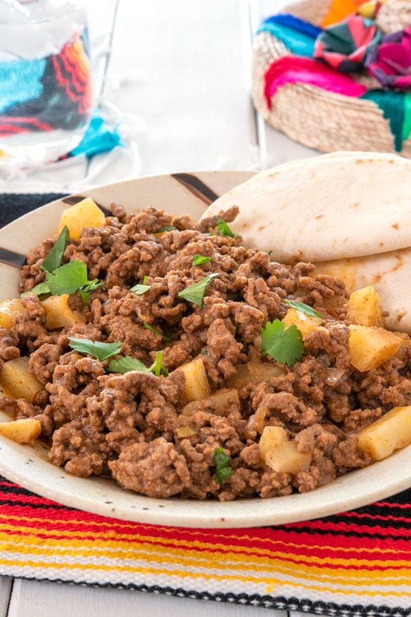 Plate of picadillo with flour tortillas on side