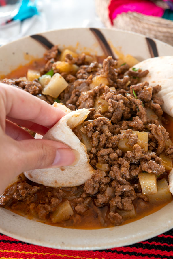 Using flour tortillas to scoop up picadillo beef