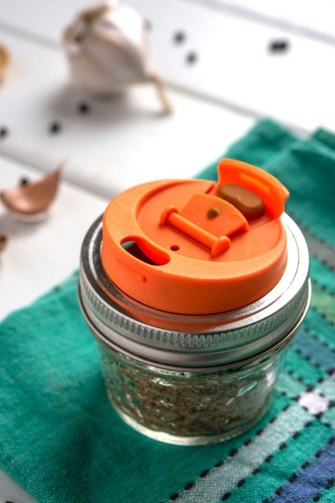 adobo seasoning in a mason jar with orange shaker lid