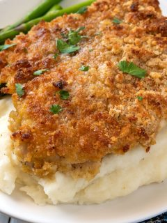 breaded chicken breast over mashed potatoes with asparagus